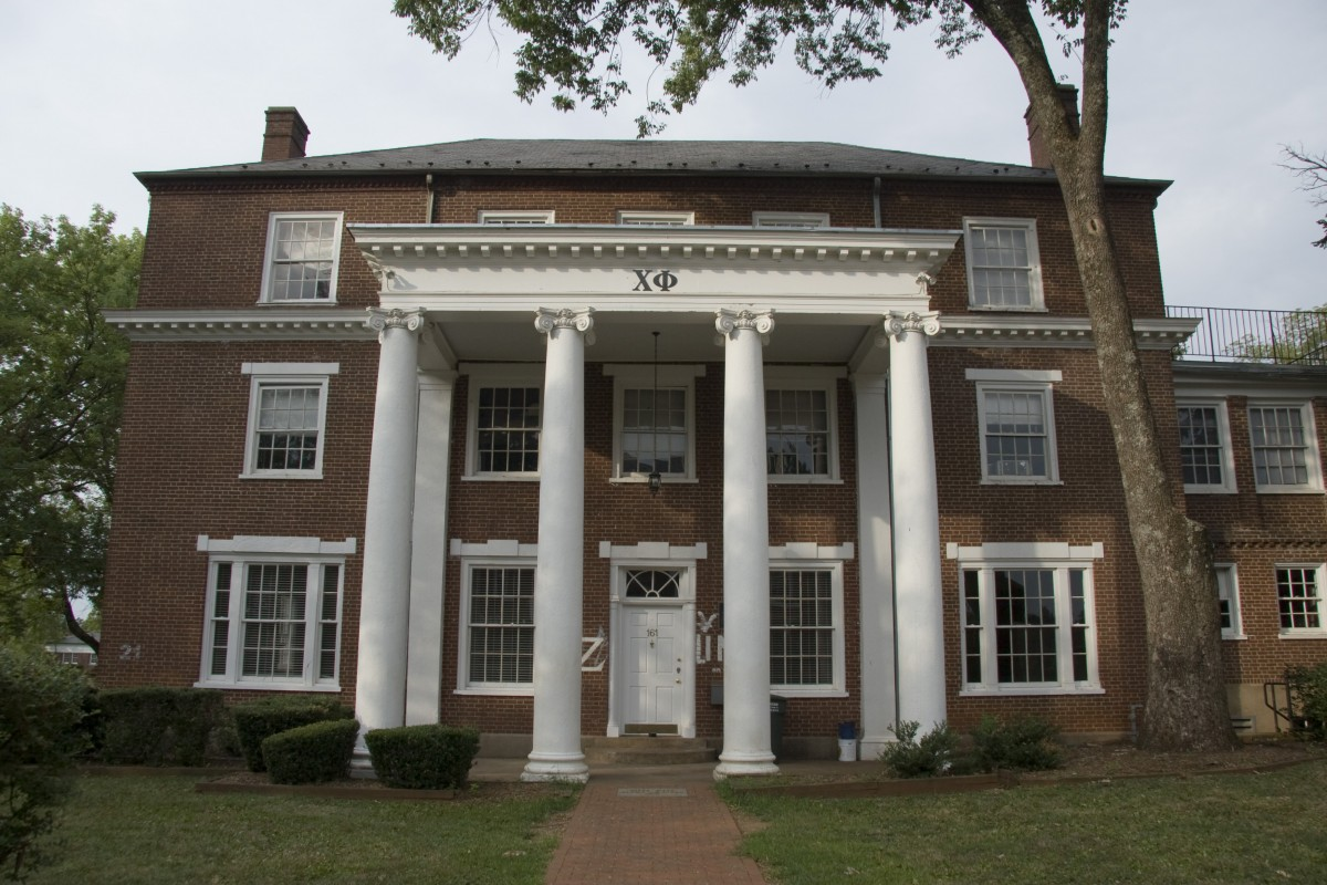 Brick three-story house with white pillars