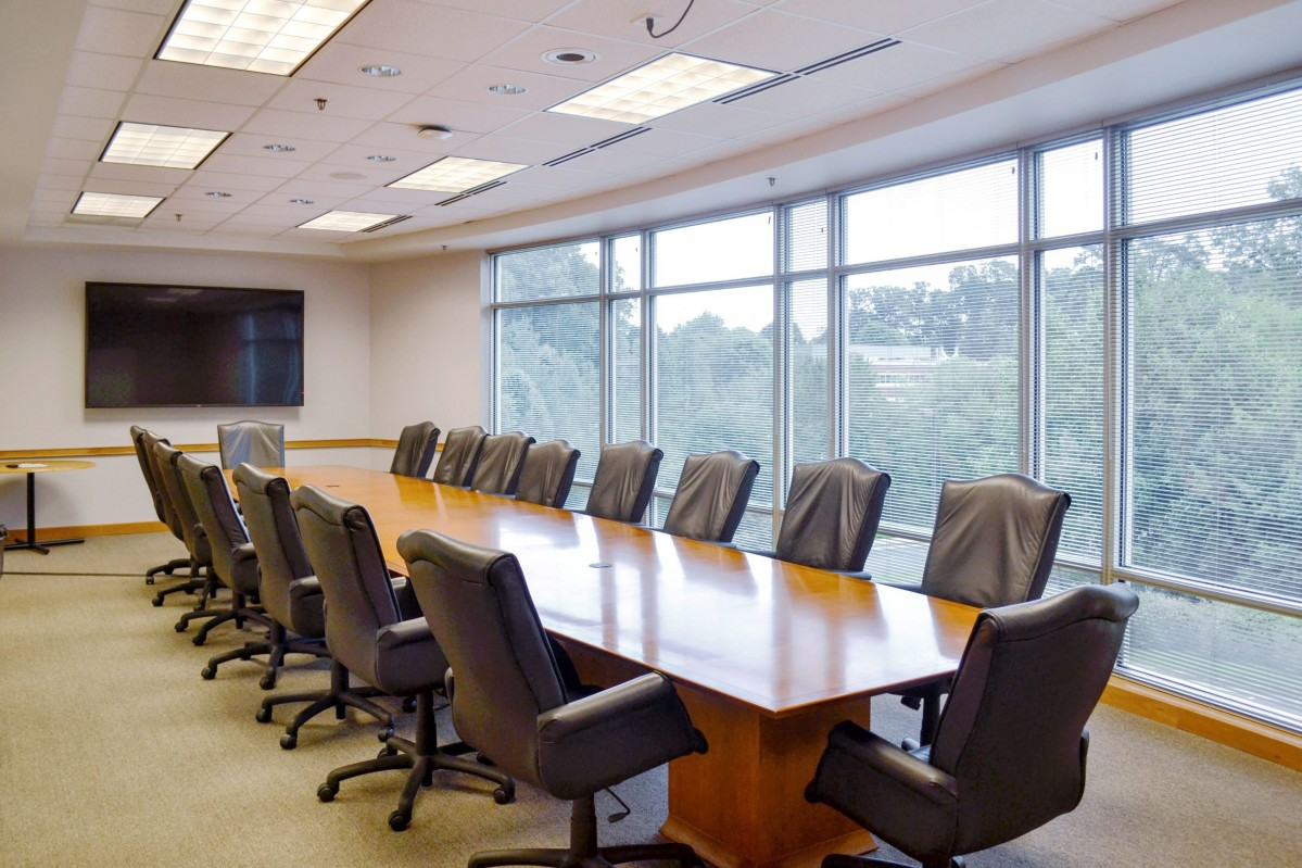 black leather executive chairs surround a long wooden conference table