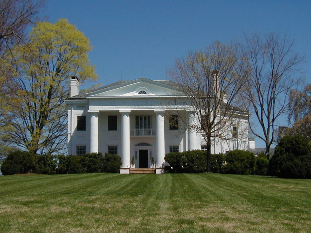 White mansion with pillars overlooking green lawn