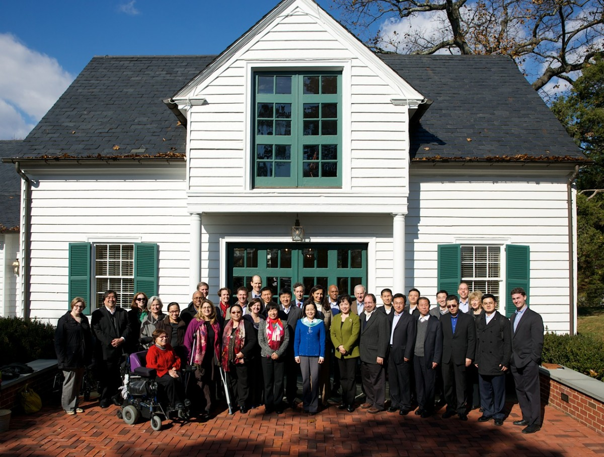 A large group gather together in front of a white barn with green trim