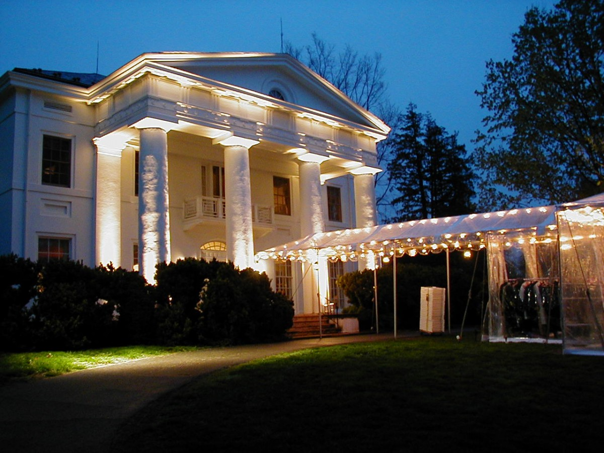 White pillared manor at dusk with party lights