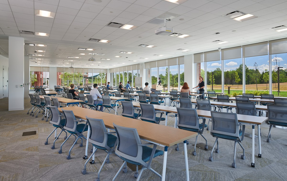 tables and chairs are arranged classroom style in a large conference room surrounded by windows overlooking the trees