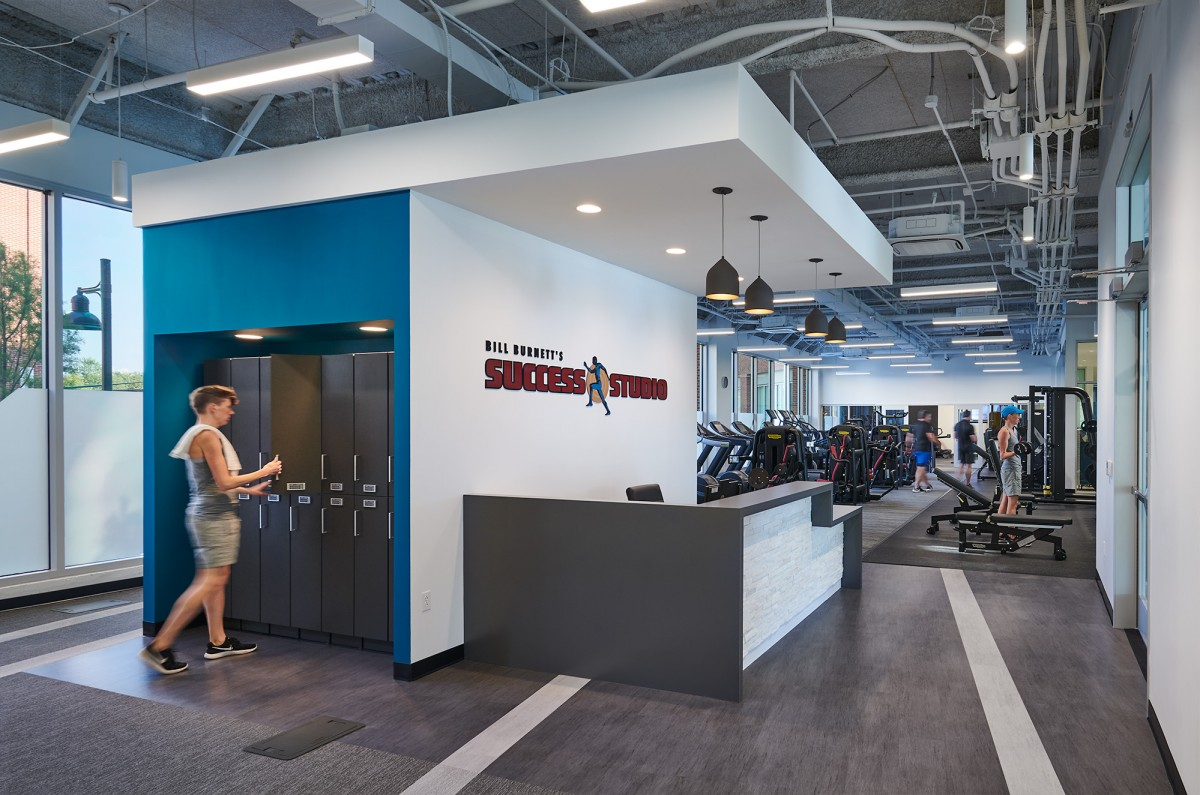 People work out in a sunny, industrial-style gym