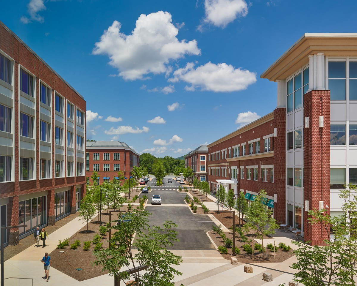 Four brick office buildings flank a boulevard and pedestrian plaza on a bright and sunny day