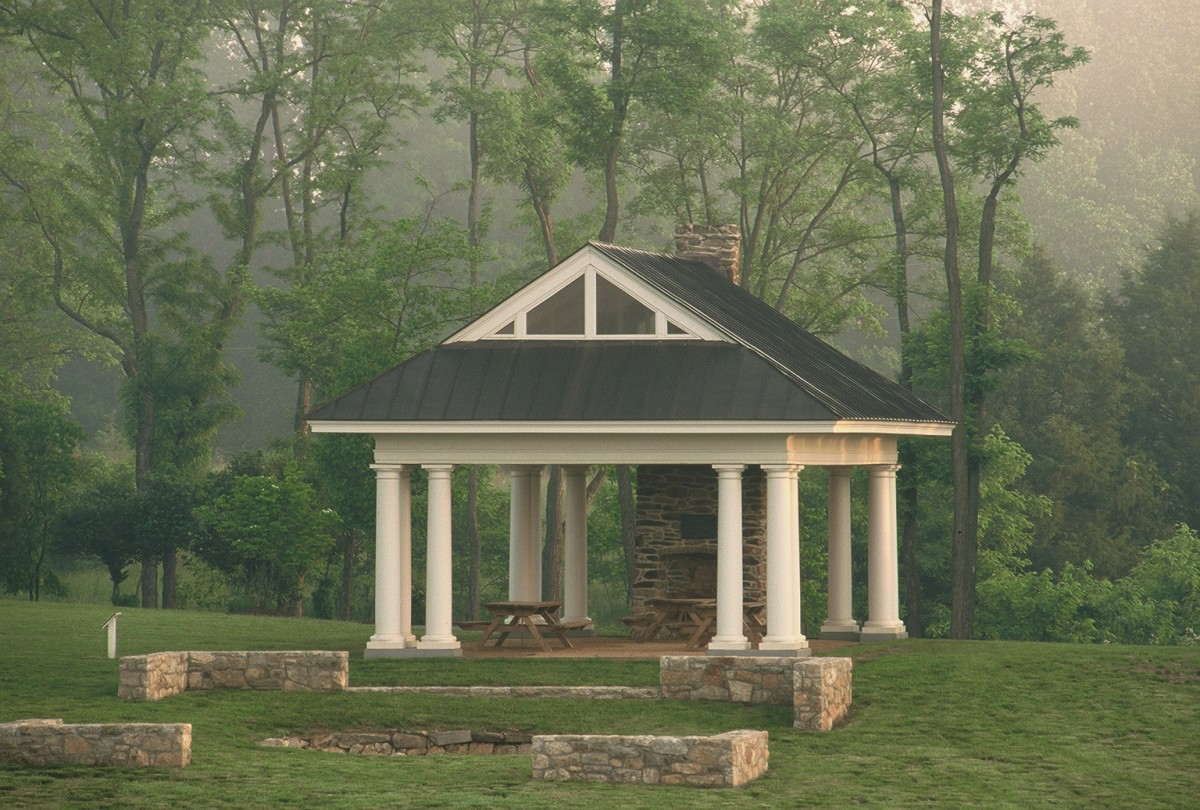 two picnic tables under a picnic pavilion with an old stone fireplace