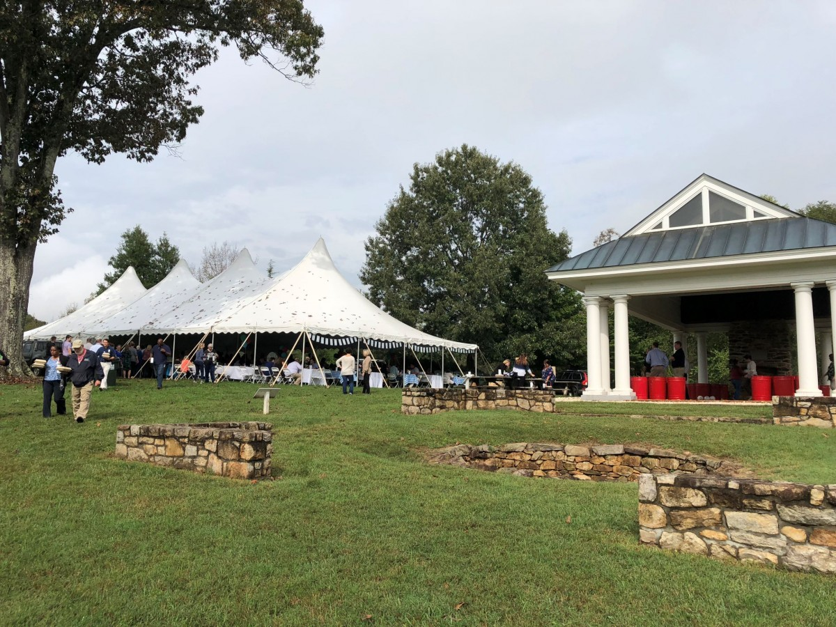 a festive white event tent sits on a green lawn while people eat and drink in early fall