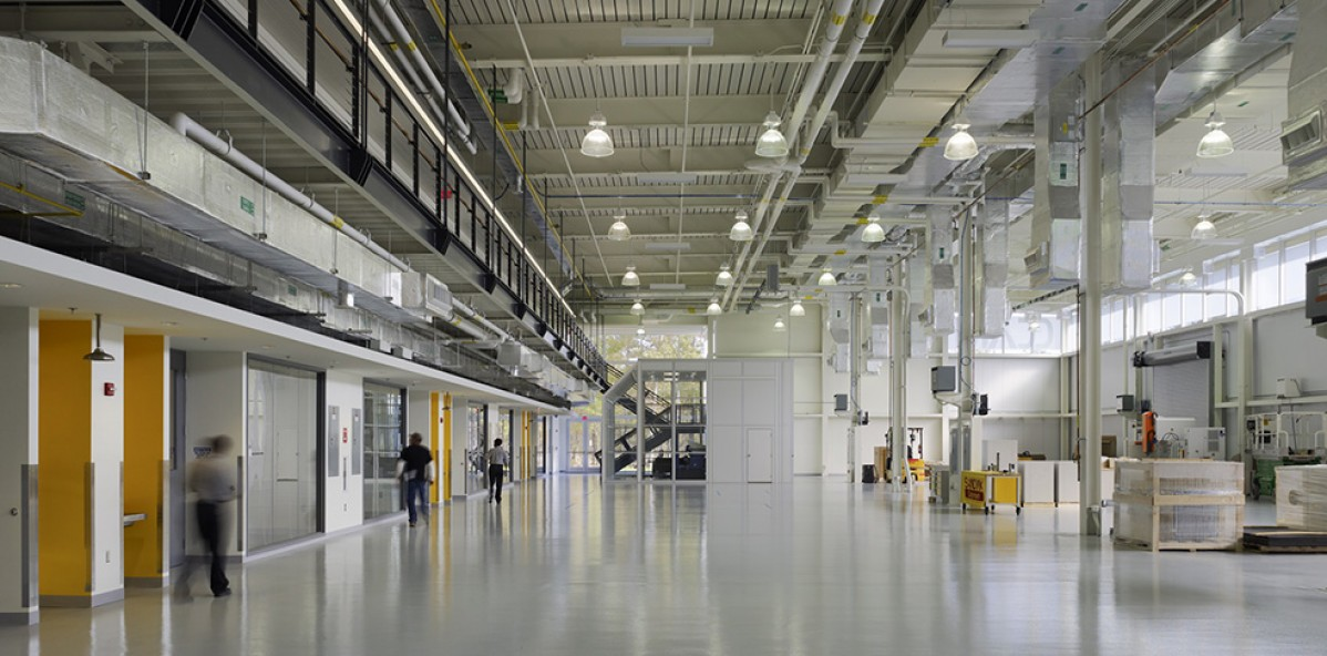 Light industrial space with white walls, open ceilings, and yellow doors