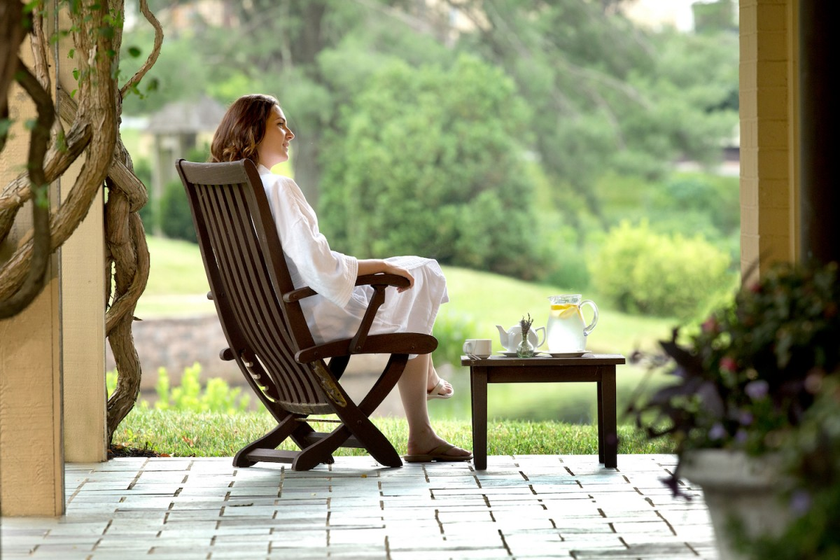 Woman in white bath robe relaxes on patio