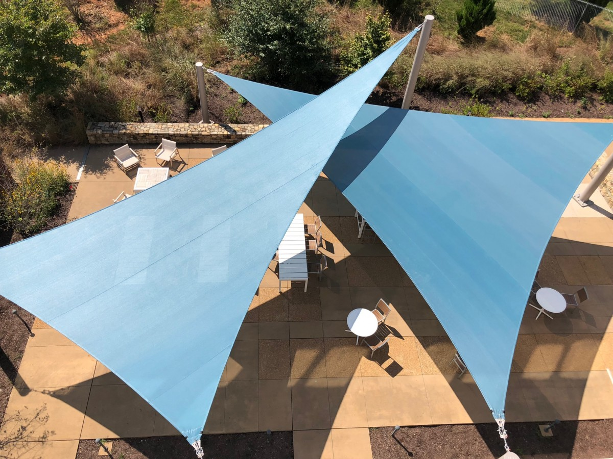 looking down on an outdoor patio shaded by large teal colored sails