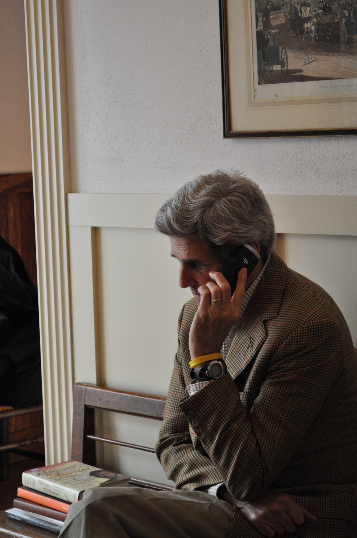 John Kerry sits a bench and holds a mobile phone to his ear