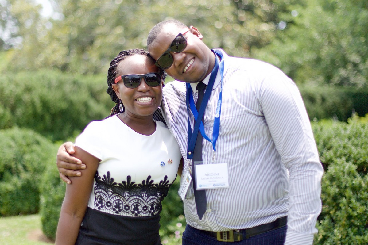 A young man and a young woman wearing glasses stand together smiling