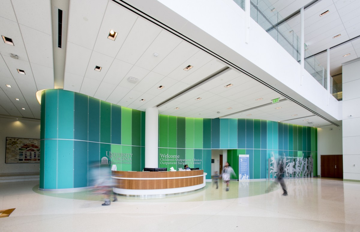Lobby of a brightly lit, modern space with a maple desk and green wall panels