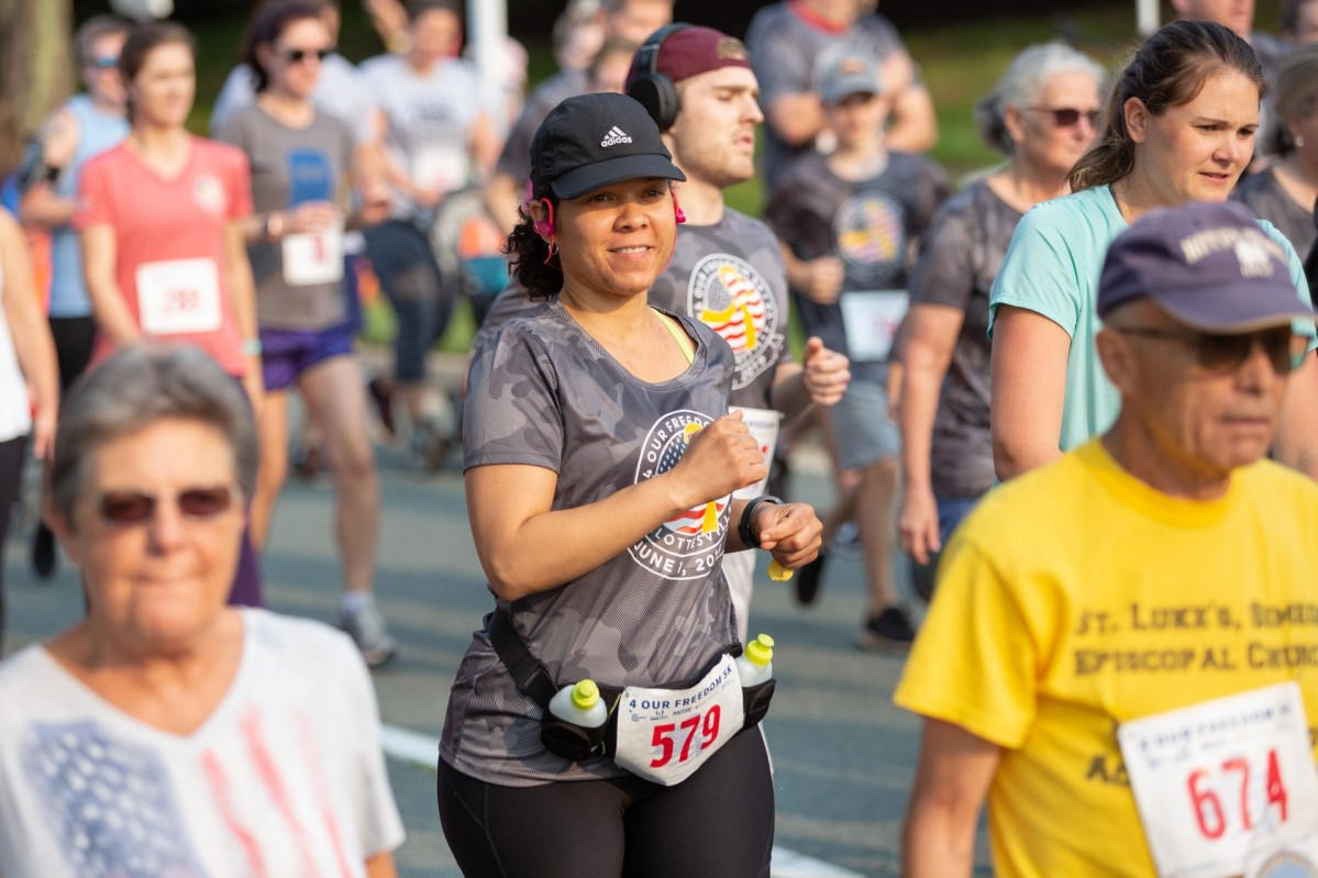 Smiling people run and walk wearing race bibs and athletic gear