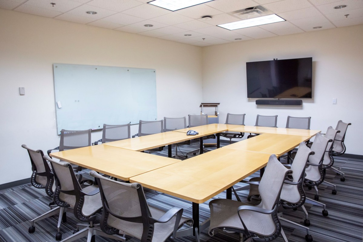 grey office chairs surround mobile oak tables in a meeting room