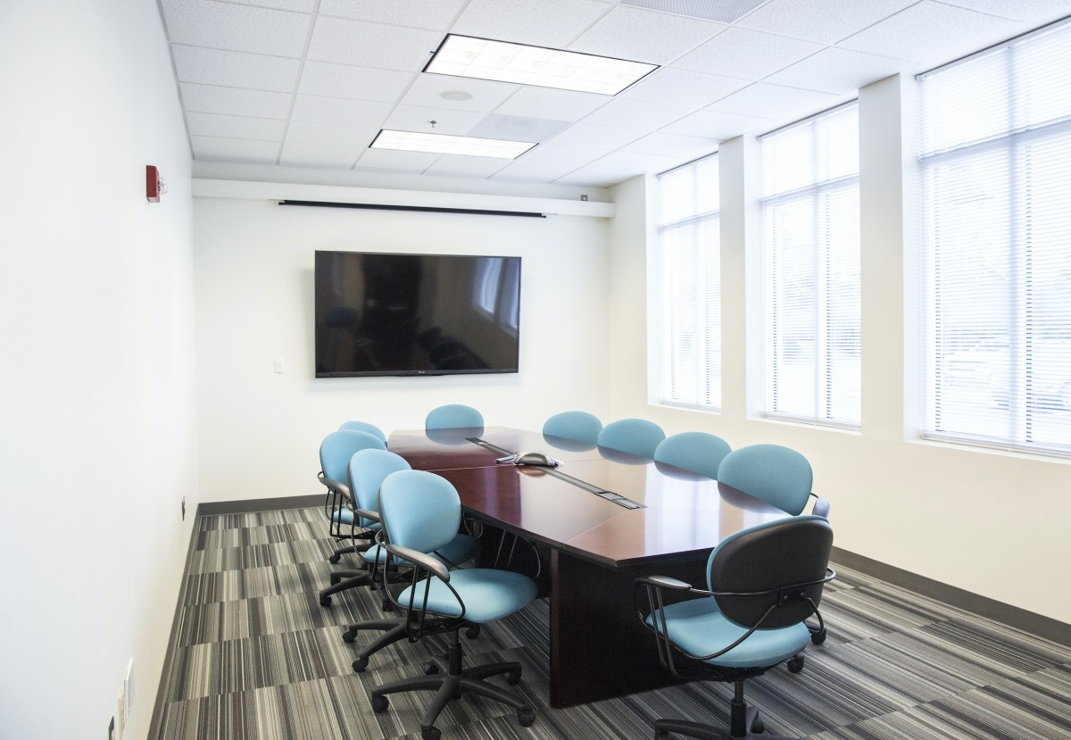 aqua colored chairs surround a polished wood conference table