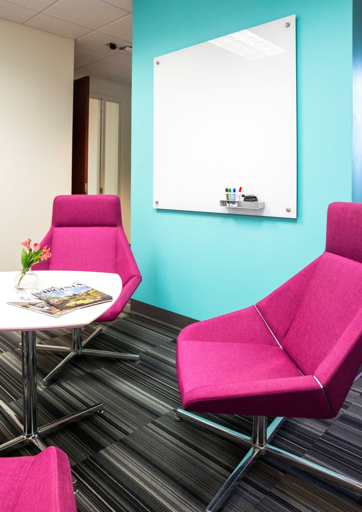 a samll room with futuristic bright pink club chairs and a glass white board on an aqua wall