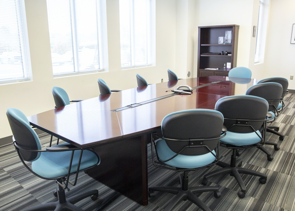 aqua colored chairs surround a polished wood conference table in a sunny white room