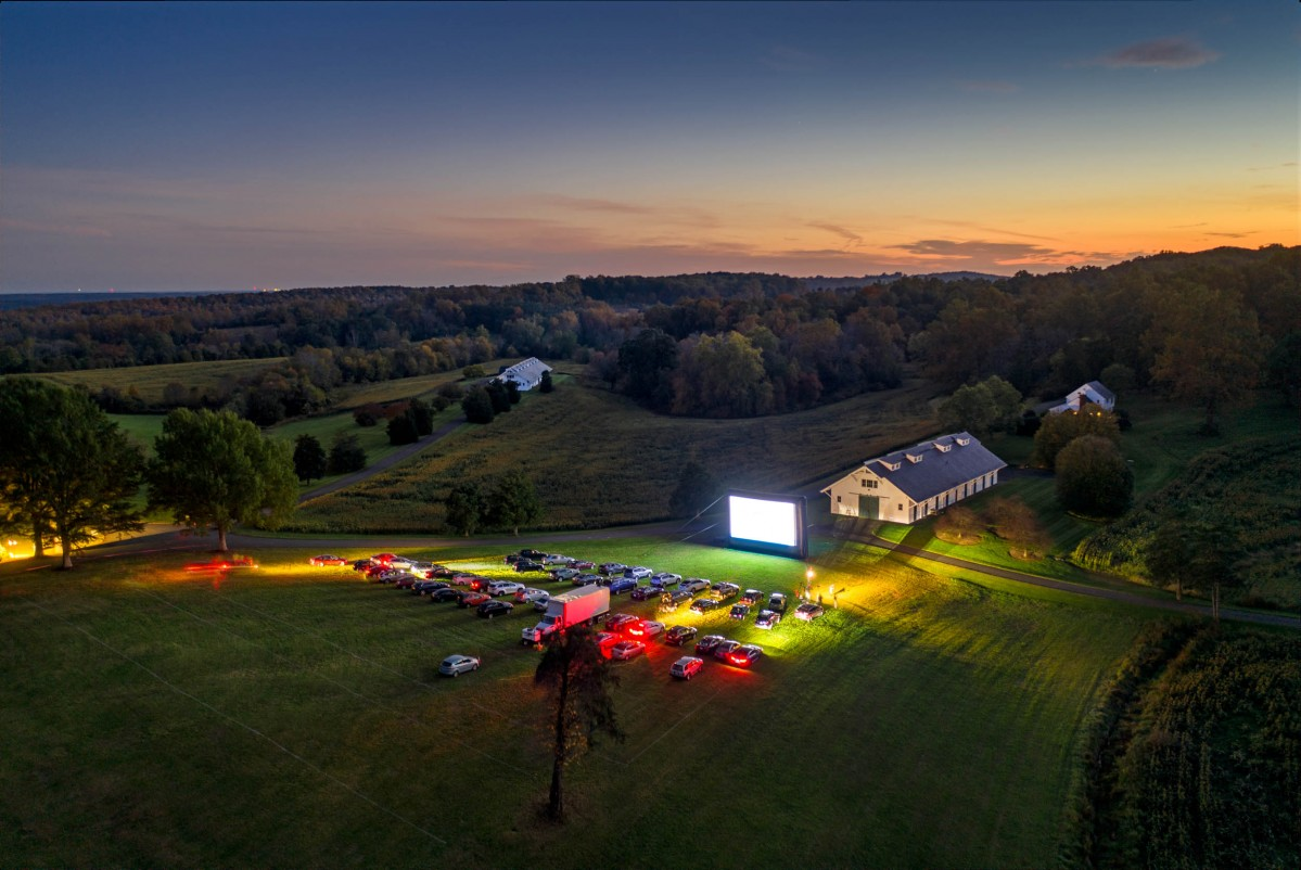 An aerial view of Morven Farm as the sun sets and cars arrive for a drive in movie